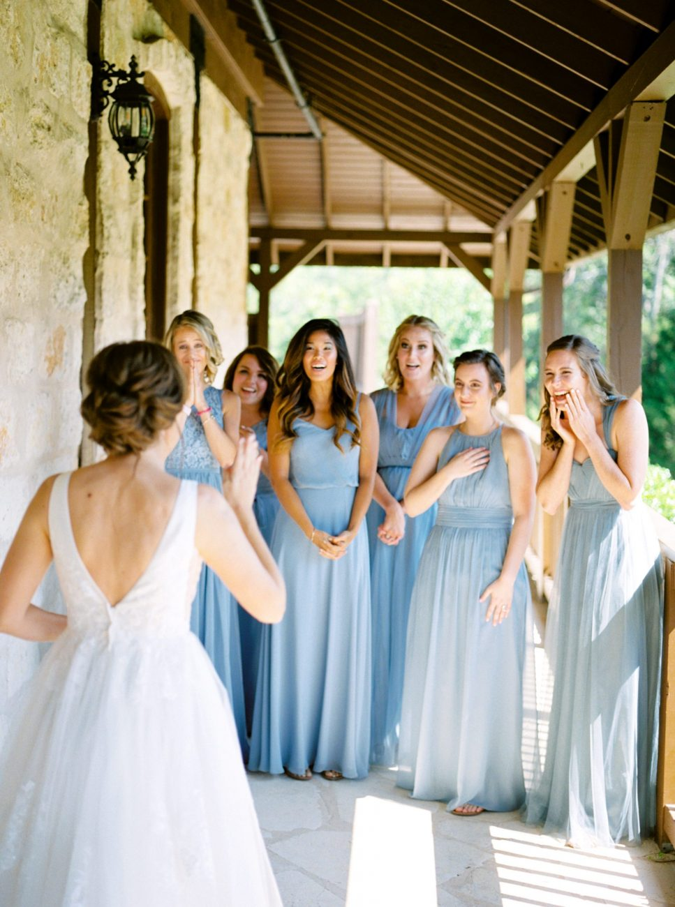 Bridesmaids in blue dresses seeing their bride for the first time at The Springs Wedding Venue.